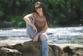 girl in torn jeans on a stone by the river