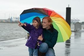 woman with child girl colorful umbrella hamburg water