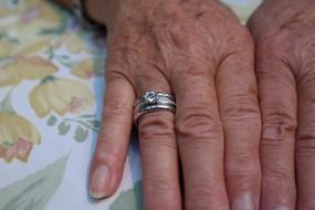 aged hands of a woman with rings