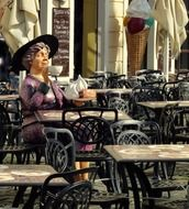 figure woman drinking tea at a table in a cafe