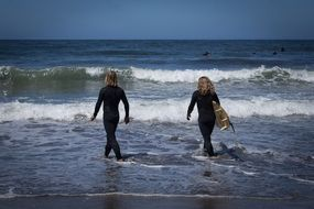 surfers, two women walking through waves