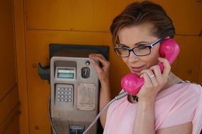 woman calling pay telephone