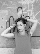 Black and white photo of a girl posing on a graffiti background
