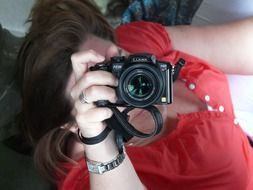photo of a girl in a red blouse with a camera