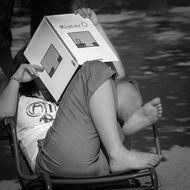 woman sits with feet on chair and reads book