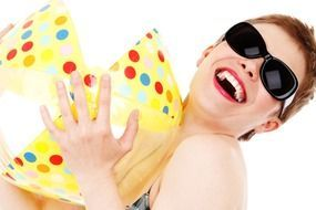 woman wearing sunglasses with a beach ball