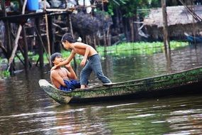 boys in a boat on Lake Tonle Sap, Cambodia