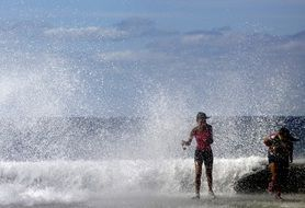 Woman running away from sea water sparkles