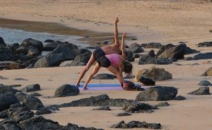 Women are doing yoga on the beach