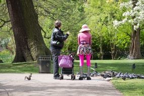 people feeding pigeon in park