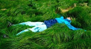 woman lying on the thick green grass