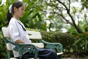 asian girl is sitting on a park bench