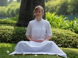 meditate woman in a white dress outdoor