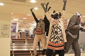 mannequins in a clothing store with arms raised