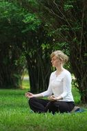 a girl who is sitting on the grass in meditation