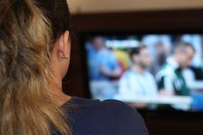 blonde girl watching football on tv