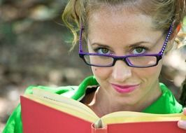 girl in blue glasses reading a book