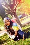 islamic girl sits on lawn in park