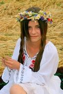 girl in the traditional suit of peasants with a wreath on her head on the background of summer nature