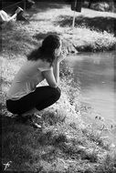 black and white photo of a girl near the lake