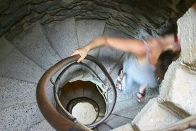 girl goes down a stone spiral staircase