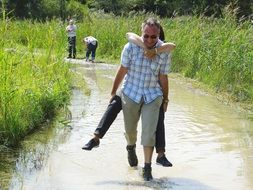 man carries a girl through a puddle