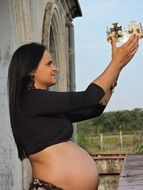 pregnant woman holding a crown