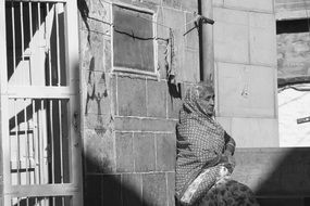 old indian woman sits at wall