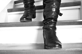 man feet in leather boots going down stairs