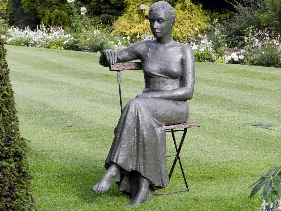 elegant woman on a chair in the park as a sculpture