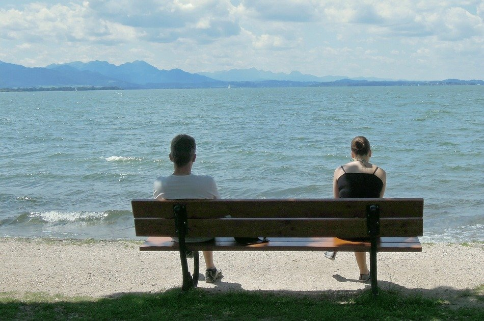 two on a bench near the lake