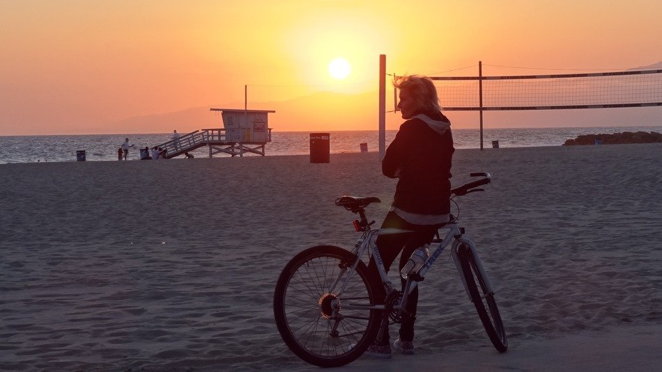 cyclist on the beach at sunset