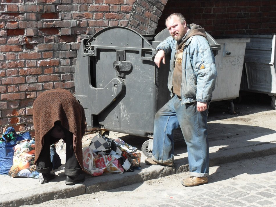 homeless couple near a garbage container in poland