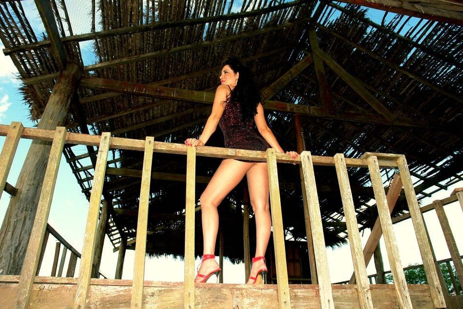 girl in a sexy dress on an open wooden terrace