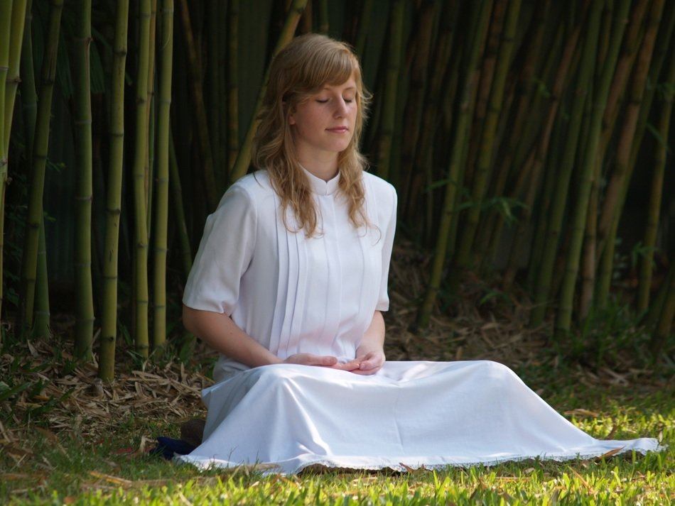 girl in white meditates among nature