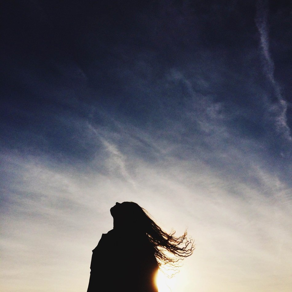 silhouette of a girl with long hair at sunset
