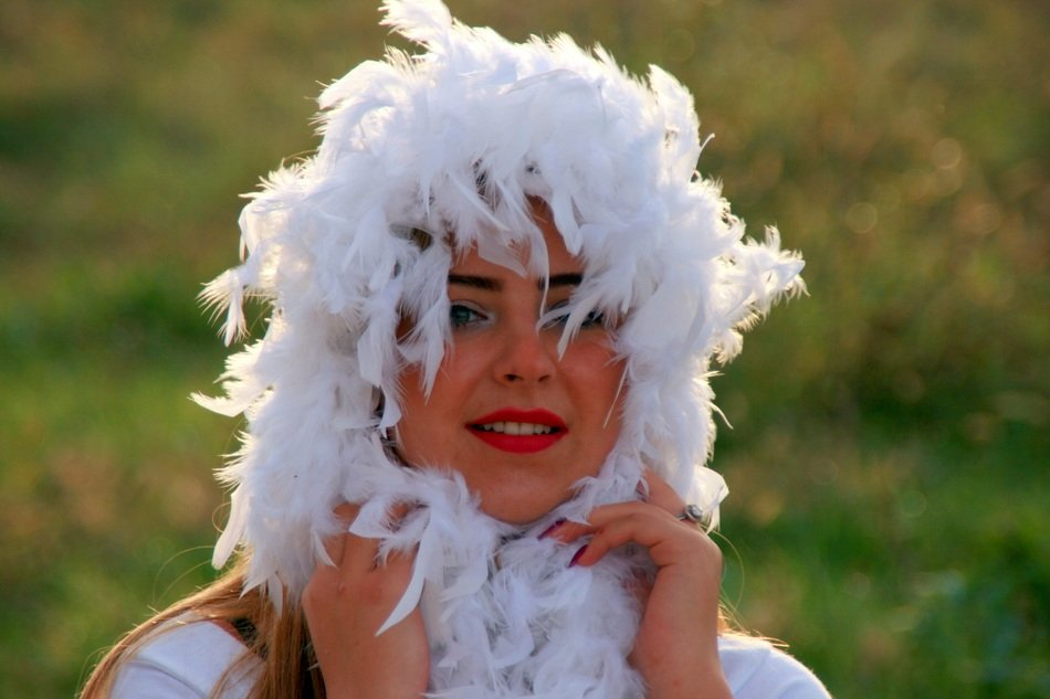 girl with bright lips in white feathers