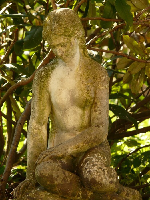 stone sculpture of a woman in the garden