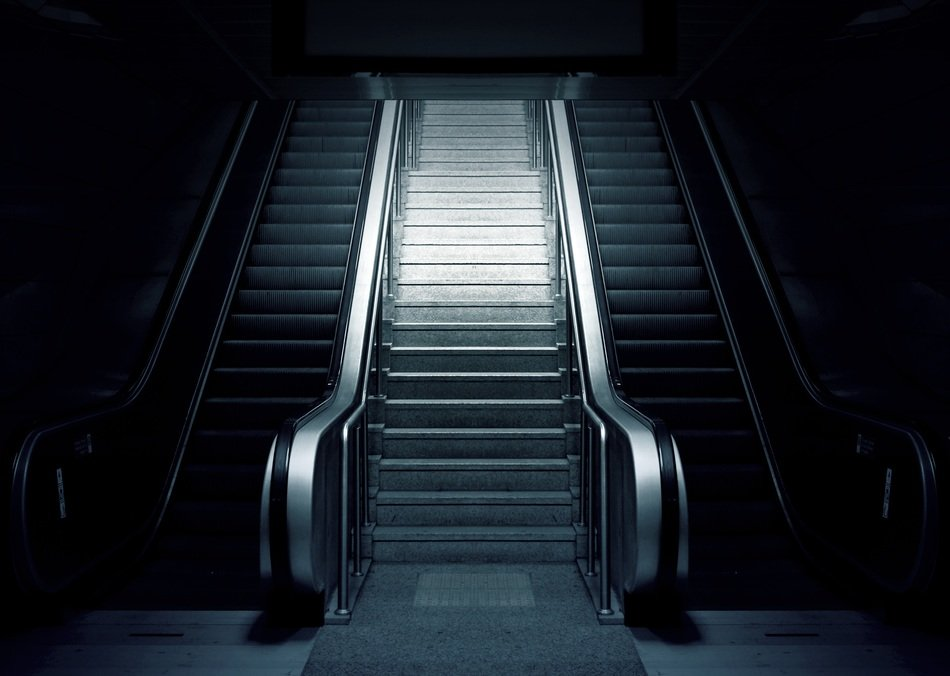 grey escalator surrounded by dim lights