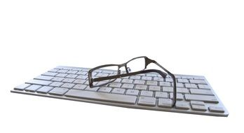 Glasses on the white keyboard