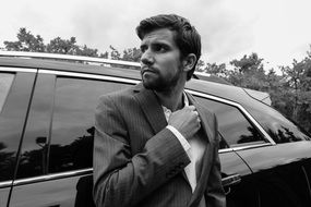 stylish beard man in suit standing near black car