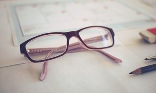 glasses lie on a document in the workplace
