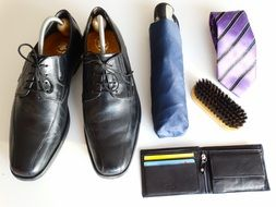 shoes, a tie, a brush for shoes, purse and umbrella