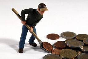 figure of a man rowing money with a shovel