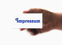 a card of impressum in the hand