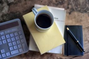calculator, notebook and cup of coffee on the books