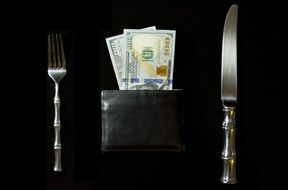 Cash in a wallet and fork with knife
