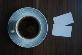a top view on a cup of coffee and business cards on the table