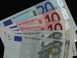 Different euro banknotes on a black background