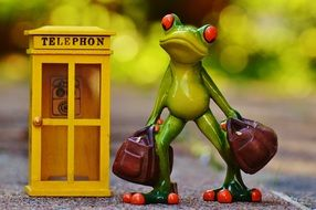 statue of a green frog with suitcases standing next to a telephone booth